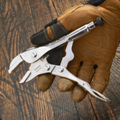 A gloved hand opening a 7 Inch straight jaw locking pliers