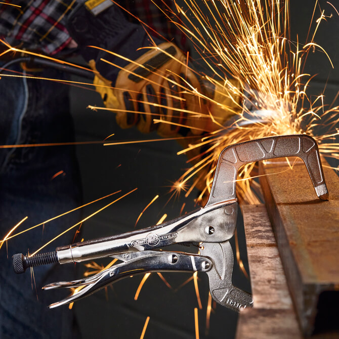 An Eagle Grip Locking C Clamp creating a vise on a piece of bar stock while a welder uses a grinder in the background creating sparks