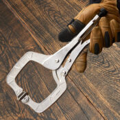 Hand wearing gloves holding an Eagle Grip C clamp with swivel pads