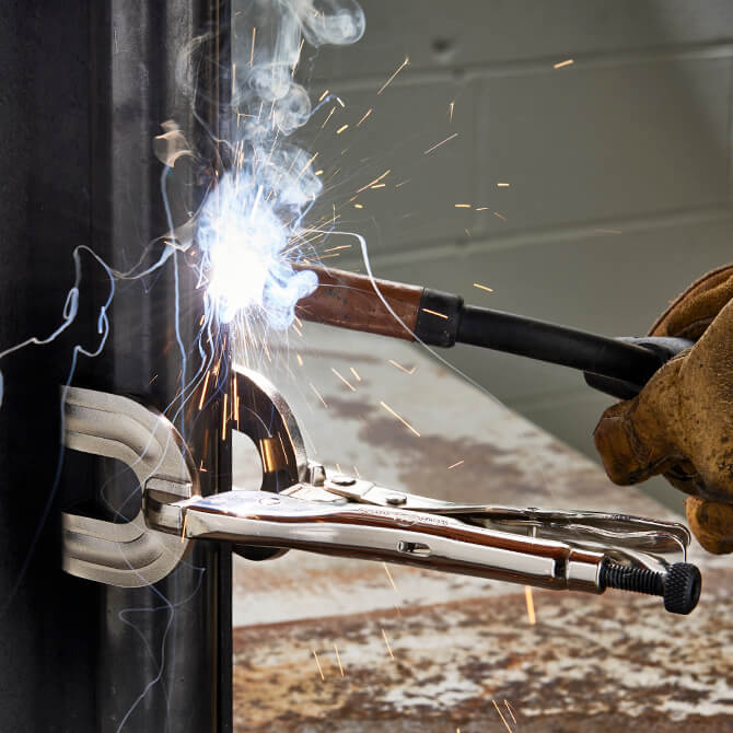 An Eagle Grip Locking Clamp with U shaped jaws vising together an angle iron while a worker uses a torch to create a weld