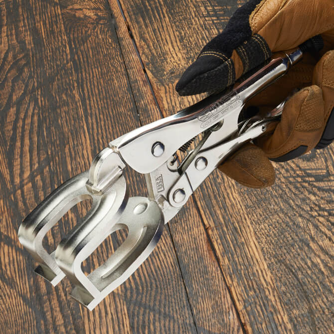 A hand wearing gloves holding an Eagle Grip Locking Welding Clamp