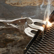 An Eagle Grip branded Locking Clamp with U shaped jaws vising together a piece of metal and mesh while a torch produces a spot weld